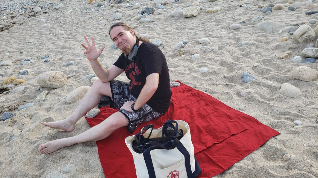 Paul waves at the camera sitting on a red blanket on the sand